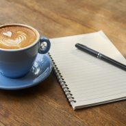 Coffee in a cup and saucer next to a note pad and pen