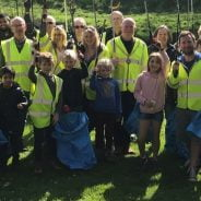 People in high viz jackets holding blue sacks and litter pickers.