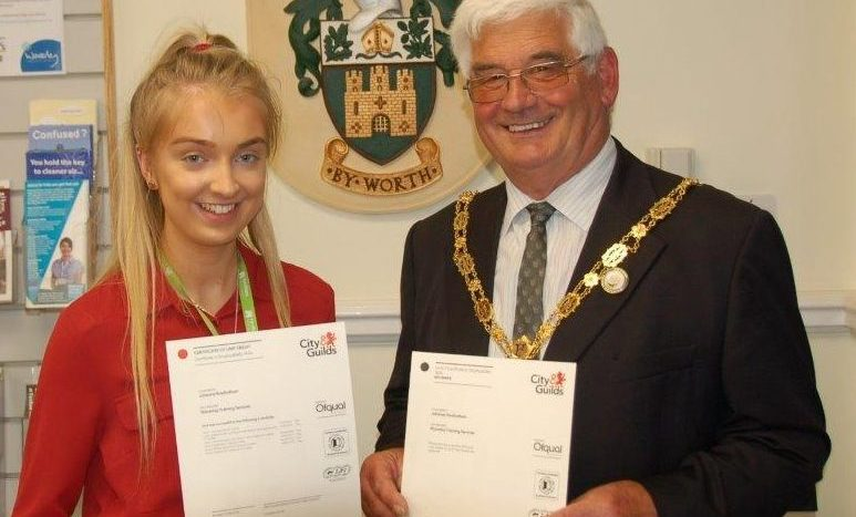Young girl holding a certificate with the Mayor on her left.