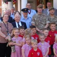 Group of children with soldiers and adults.