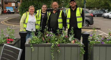 Four people standing behind a flower planter.