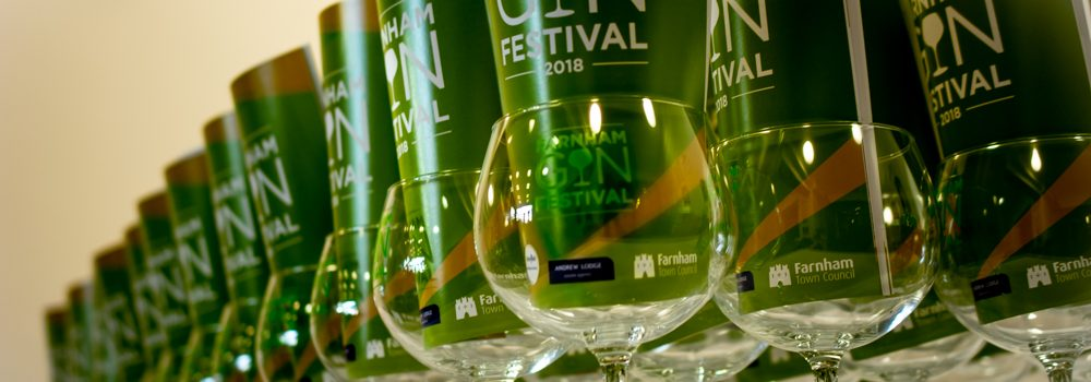 Row of stemmed glasses with a green Gin Festival programme inserted in each