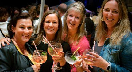 Four females holding gin glasses.