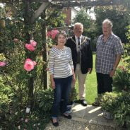 Female, Mayor and male stand under an archway in a pretty garden.