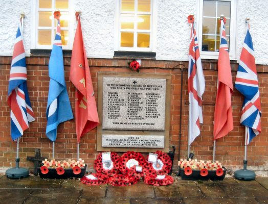 Stone war memorial embedded in the wall of a building. Three flags either side of memorial and poppy wreaths at the base.