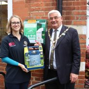 Female and Mayor holding a defibrillator in a box