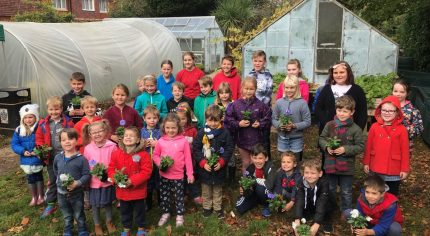 Children standing in front of an allotment holding potted plants.