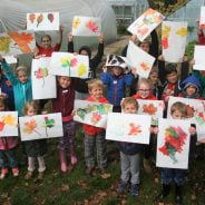 Children holding paintings of leaves.