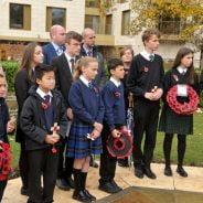 School children holding poppy wreaths