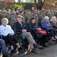 Older people in wheelchairs and soldiers standing behind.