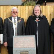 Mayor, men in uniform and vicar at a war memorial.
