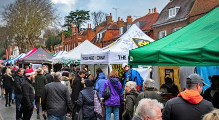 Crowd of people at an outdoor market. Colourful gazebos in street
