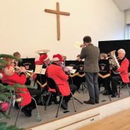 Brass band sitting on a stage wearing Christmas hats.