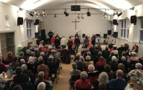 Older people watching a band perform inside a church hall