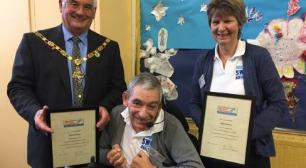 Man in wheelchair with the Mayor and a female holding certificates.