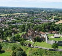 Aerial photo showing castle and green spaces and trees.