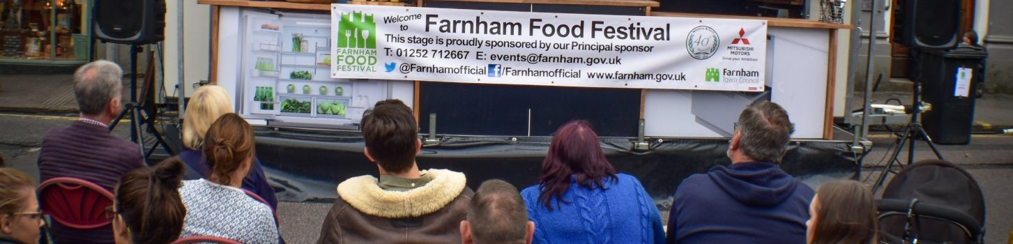 People sitting in front of a stage watching a Food Festival demonstration.
