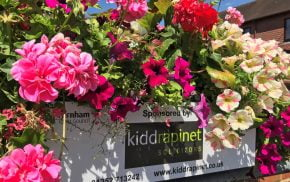 Close up of pink, purple and white flowers in a trough with a plaque on the container showing a sponsor's name.