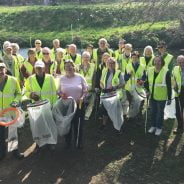 Group of people in high viz jackets holding sacks and litter picks