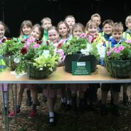 Group of children standing behind a table full of hanging baskets.