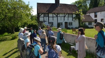 Group of walkers outside a timber framed house