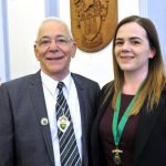 Smiling man in suit wearing a deputy Mayor's badge standing next to female.