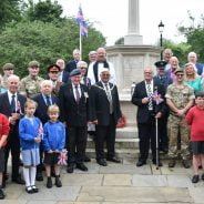 Group of adults and children standing in front of war memorial