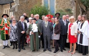 Mayor with group of people in smart clothes standing outside church.