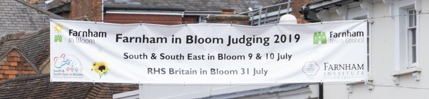 Cross street banner announcing the dates of Farnham in Bloom judging.