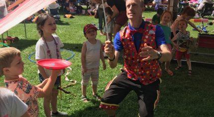 Juggler spinning a hat. Children watching.