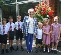 School children with the Mayor of Farnham in front of a hanging basket.