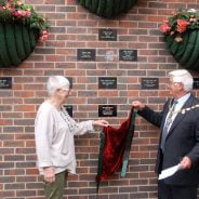 Mayor and female remove a drape to unveil a plaque on a wall.