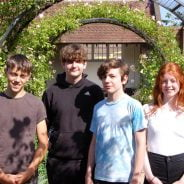 Four young people in a garden.