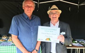 Two men in a marquee. Man on right presents a certificate.