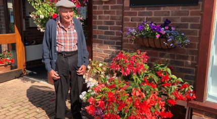 Elderly man standing next to container overflowing with red flowers and plants.