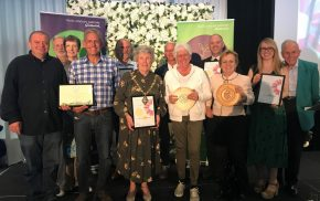 Group of people holding certificates and trophies