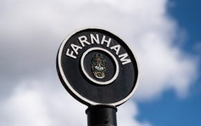 Black circular sign post with Farnham painted in white letters around top of circle