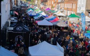 Aerial view of crowded street market and colourful marquees