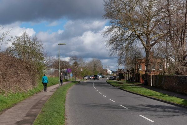 View along a tree lined road. People walking on the grass lined footpath.