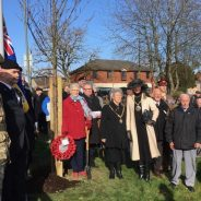 Group of people standing in semi circle. Trees and union flag in background
