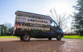 Van wrapped in floral vinyl and parked on gravel