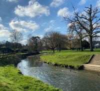 Meandering river, grass banks, blue sky and trees in background. Winter