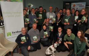 Group of people holding a booklet. Dog in foreground