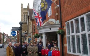 Group of adults and children in front of building. Commonwealth flag and Union flag flying on side of building
