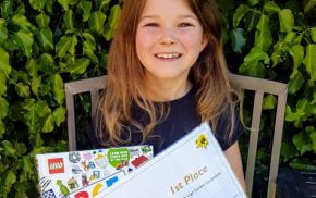 Girl sitting on bench in garden holding a certificate and lego prize.