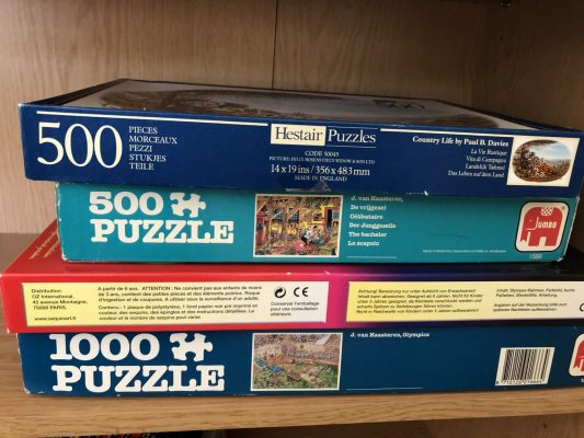 Four boxes of jigsaw puzzles stacked in a pile
