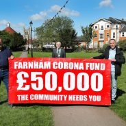 Three men holding banner advertising fundraising appeal