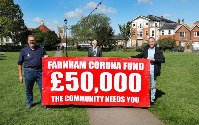 Three men holding banner advertising fundraising appeal