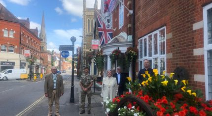 Armed Forces Day flag raising ceremony. Five people standing outside the town hall. Armed forces day flag and the Union flag are flying. Colourful flowers in a hop cart in the foreground.
