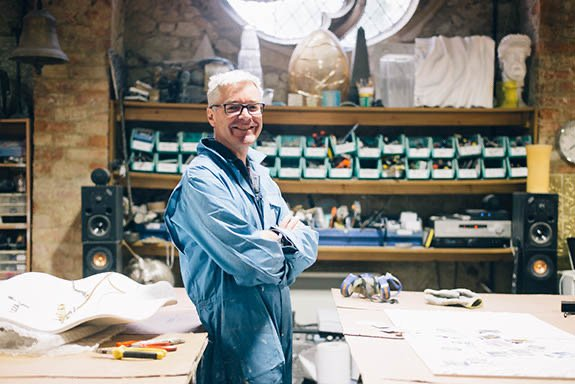 Smiling man wearing overalls standing in a workshop